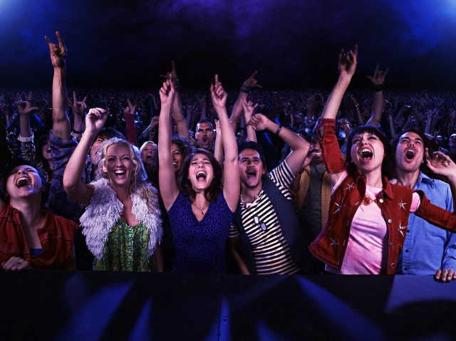 Fans at a concert singing and having a fun time
