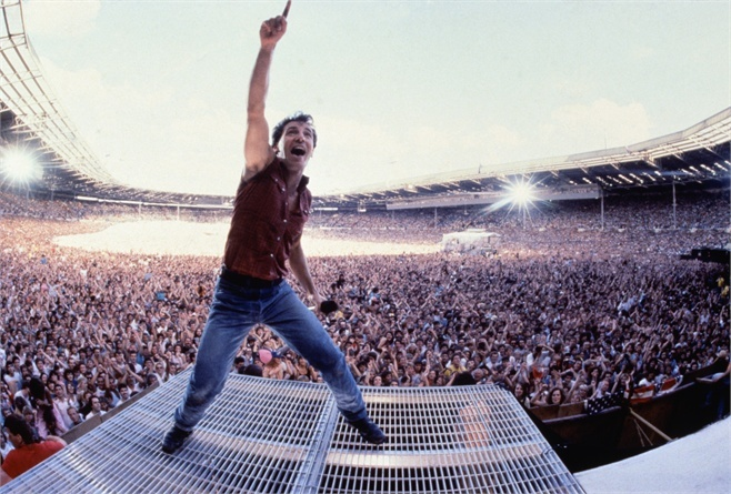 "Bruce Springsteen, known as ""The Boss,"" plays a large stadium during one of his four hour concerts"
